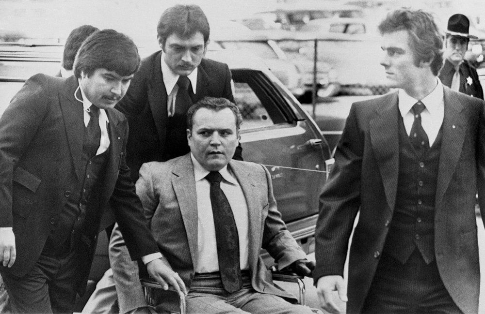 "FILE - ""Hustler"" magazine publisher Larry Flynt is surrounded by heavy security as he arrives at the Fulton County Courthouse in Atlanta on March 19, 1979, for the start of his trial on obscenity charges. Flynt, who turned ""Hustler"" magazine into an adult entertainment empire while championing First Amendment rights, has died at age 78. His nephew, Jimmy Flynt Jr., told The Associated Press that Flynt died Wednesday, Feb. 10, 2021, of heart failure at his Hollywood Hills home in Los Angeles. (AP Photo/Steve Helber, File)"