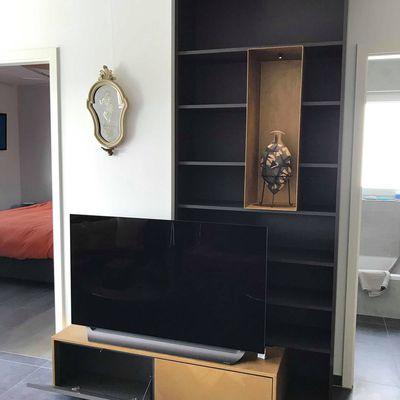 mobilier de salon en noir et or avec niche débordante en métal et interrupteur led intégré