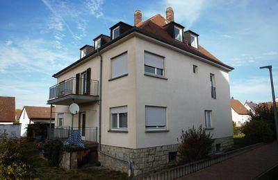 Seit zwölf Jahren leerstehendes Gemeindemiethaus Würzburger Straße 58 soll in geplante Seniorenwohnanlage auf dem Grundstück des alten Rewe-Marktes einbezogen werden