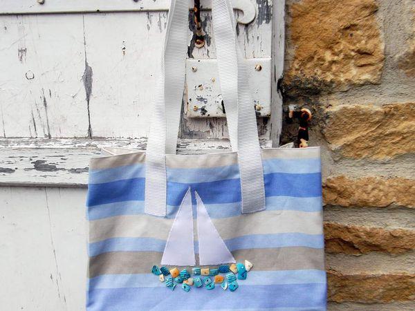 Sac de plage en toile rayée, doublure coton écru, anses synthétique 60 cm. Fond en molleton de polyester. Bateau : voiles coton appliqué, coque coquillages teintés et perles de rocaille. Dimensions : 25 h x 37 L x 10 l cm - Prix 20 € + Frais de port - Pièce unique