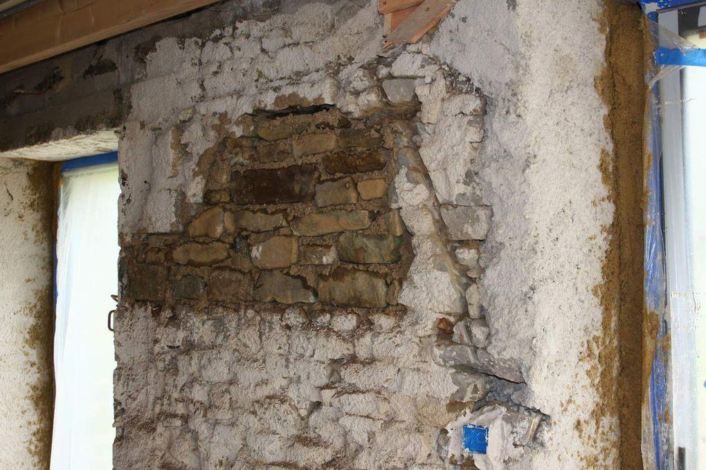 Pour cette rénovation les murs qui donnent sur l'extérieur ont été traités avec un enduit chaux chanvre. Les murs entre deux espaces chauffés ont été traités avec un enduit chaux/terre/chanvre et sable. Un gobetis chaux sable a été réalisé sur la pierre, pour les parties bétonnées il y a eu un ajout de ciment dans le mélange. L'électricien a réalisé le rainurage dans les murs pour passer les gaines électriques, les boîtiers électriques ont été scellés avec du plâtre. Après quelques jours de séchage le chaux chanvre et la couche de corps à base de terre ont été appliqués et réglés sur les murs. Enfin après plusieurs mois de séchage les enduits de finitions ont été réalisés à base de chaux/sable/paillettes de lin et sur quelques murs il a été réalisé un enduit teinté avec de la terre. Au sol le béton ciré (réalisé par intérieur ciment) de couleur marron se marie parfaitement bien avec les enduits et les murs peints.
