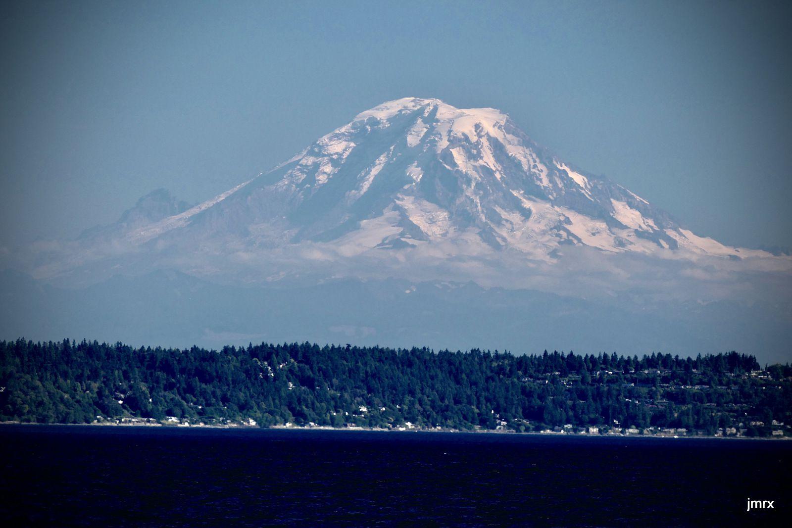 Le Mont Rainier (4400m) semble flotter dans l'air du soir. Un peu plus loin on distingue le port industriel de Tacoma.