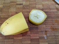 2 - Laver, sécher et équeuter les fraises. En découper 3 en petits dés, réserver le reste. Une fois la pralinoise autour de la banane bien sèche, retirer avec précaution le reste (les 2/3) de la peau de banane. Découper 9 rondelles dans les surplus de bananes. Oter les bouts de chaque fraise pour qu'elles puissent tenir droites et évider le centre à la cuillère parisienne.