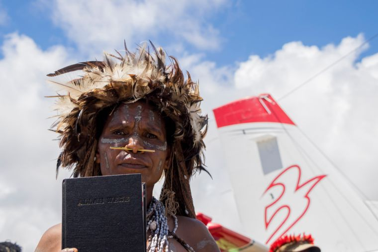 Une femme en tenue tribale traditionnelle tenant la Bible en langue yali à Apahapsili, en Papouasie, en Indonésie (Photo: Mission Aviation Fellowship)