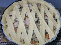 3 - Préchauffer le four th 6,5 (200°). Foncer un moule à tarte avec la pâte feuilletée, piquer le fond à la fourchette. Répartir la préparation poulet légumes dans la tarte. Dans la 2ème pâte feuilletée, découper 10 bandes d'environ 1,5 à 2 cm de large (vous pourrez utiliser le reste de pâte pour réaliser des petits feuilletés apéritif avec des graines : pavot, sésame ....). Disposer les bandes en formant des croisillons, couper le surplus de pâte et bien souder les bords avec une fourchette. Allonger le jaune d'oeuf avec une cuil. à soupe d'eau et bien dorer les croisillons. Enfourner pour 20 à 25mn environ en surveillant pour obtenir une tourte bien dorée. .