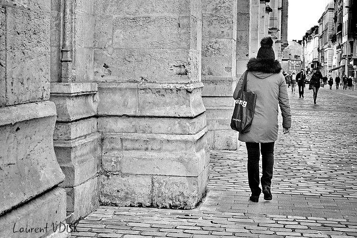 Passant avec bonnet à pompon devant le palais de justice de Rouen.  Noir et blanc.
