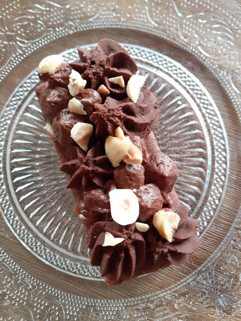 Tartelettes caramel au beurre salé, ganache chocolat, ganache pâte à tartiner et noisettes sur un palet breton chocolat