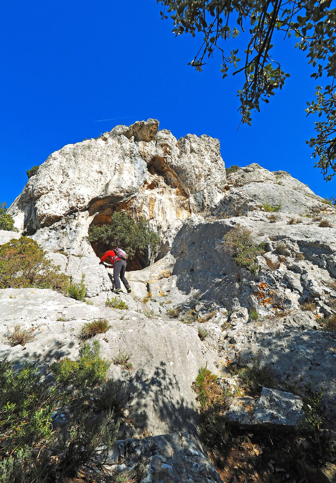 C'est peu après ces vires que l'on peut monter quelques mètres sur la gauche du chemin pour voir la grotte. Une petite escalade facile d'une dizaine de mètres y donne accès. On peut aussi passer par une vire plus à gauche.
