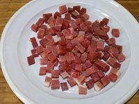 1 - Mettre le four à préchauffer th 6,5 (200°). Peler et dégermer l'ail, le hacher. Tailler le jambon serrano en petits dés. Mettre l'huile d'olive dans une grande poêle. Y faire revenir l'ail, puis le jambon 1 à 2 minutes en remuant. Rajouter le pain coupé en tranches et mélanger pour que le pain s'imprègne des saveurs de l'huile, de l'ail et du jambon et qu'il dore un peu. Incorporer le pimenton (piment espagnol) remuer rapidement afin qu'il ne grille pas et rajouter l'eau pour bien recouvrir tous les ingrédients. Porter à ébullition et laisser cuire 3 à 4 mn. Assaisonner avec sel et poivre.