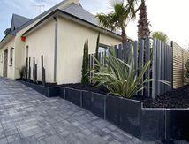 Aménagement d'une entrée en pavés multi formats et mur en dalles de ardoise. Plantation de palmiers et installation de brise vue en ardoise et bois