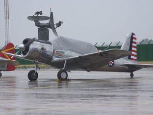 """Sous sa bache, le Vultee Valiant basé à Chambley et les avions de l'association """"Répliques Volantes de la Grande Guerre""""."""