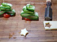 1 - Laver et sécher le concombre (de préférence bio). Le tailler en fines lamelles dans le sens de la longueur. Les couper en deux au centre toujours dans la longueur. Couper les tomates cerises en deux. Enfiler une lamelle de concombre en accordéon sur une pique en bois comme sur la photo. Piquer une moitié de tomate cerise à la base. Détailler des étoiles dans les tranches de fromage à l'aide d'un emporte-pièce de cette forme. Passer rapidement au grill du four quelques tranches de pain de mie pour les faire dorer.  Les sortir et laisser refroidir quelques instants. Réaliser de petits disques dans les tranches de pain de mie avec un emporte-pièce rond.  Déposer une noisette de mayonnaise sur les disques de pain de mie, piquer dessus le montage sapin tomate/concombre, enfiler l'étoile en fromage en haut de la pique et terminer en disposant quelques oeufs de lump rouges aux extrémités des lamelles de concombre.