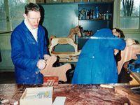 """Les étapes de la construction d'un cheval à bascule du façonnage méticuleux de la tête aux assemblages sous presses des panneaux constituant membres, flancs et assise avec ajout final de la queue et des éléments de balancement entretoisés - Laurent M. ébarbe les contours de la tête - Robert a effectué la séparation des oreilles à la queue de rat - Jean-Claude polit les parties jointes des flancs qui ont été maintenues sous presse pendant 24 heures - Thierry effectue à la lime les chanfreins sur les contours du """"chevalet"""" que l'on voit, plus loin, complété avec la tête et la queue. L'ensemble est poncé au papier de verre par Eric F. puis par Eric T."""