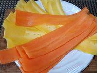 1 - Laver et éplucher les carottes. Les tailler en fines bandes de largeur identique. Couper les bords bien droits pour un beau rendu.  Les placer à plat l'une sur l'autre en les décalant comme sur la photo (la bande du dessous doit être un peu plus longue que l'autre). Les enrouler sur elles-mêmes, les redresser et les maintenir en rouleau avec une pique en bois.