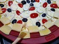 3 - Mettre le four à préchauffer th 6/7 (200°). Prendre un moule rond en silicone (ou autre) avec des rebords plats. Y disposer la pâte et piquer le fond à la fourchette. Ajouter successivement : une couche d'emmental râpé, les poireaux et échalote cuits, les tomates et oeufs joliment répartis, ainsi que les olives noires. Terminer en versant délicatement l'appareil sur le tout. A l'aide d'une paire de ciseaux découper les rebords de la pâte comme sur la photo en alternant la disposition des rectangles à l'intérieur et à l'extérieur. Les badigeonner au pinceau de beurre fondu et y parsemer des graines de pavot. Mettre à cuire au four pendant 25 mn environ jusqu'à ce que la tarte soit bien dorée.