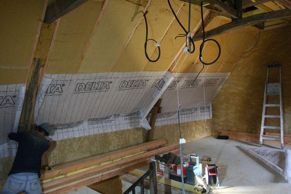 Restauration d'une maison en terre à BAIS. Une couche de corps en terre/sable/chaux/chanvre a été réalisée au RDC et à l'étage. En isolation des rampants 2 couches croisées de laine de bois 145mm (29cm total) avec le frein vapeur. Un adhésif CONTEGA pro clima (couleur bleu) a été utilisé pour faire la jonction d'étanchéité à l'air entre le frein vapeur et la couche de corps en terre. Le placage et l'enduit de finition seront réalisés en début d'année.... A noté la condensation à la sous face des ardoises (côté chaud) sur une des photos, d'ou l'importance de mettre en place une ventillation sous toiture.