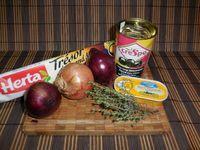 1 - Préchauffer le four th 7. Eplucher et émincer les oignons. Les faire revenir dans une poêle avec du beurre à feu moyen jusqu'à ce qu'ils deviennent translucides. Remuer de temps en temps, ils ne doivent pas griller. Couper en petits dés une vingtaine d'olives noires pendant la cuisson des oignons. Une fois cuits, mettre les oignons dans une jatte, y ajouter les olives coupées, le thym émietté, le poivre et une petite pincée de sel. Bien mélanger le tout.