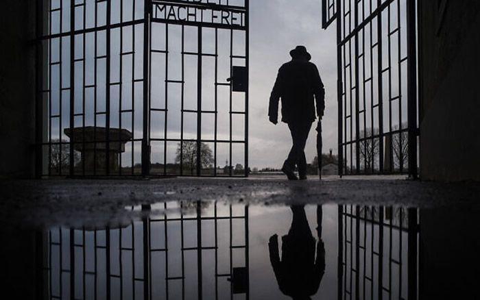 Un homme franchit la porte du camp de la mort nazi de Sachsenhausen avec la phrase « Arbeit macht frei » (le travail rend libre) à Oranienburg, en Allemagne, lors de la Journée internationale de commémoration de la Shoah, le 27 janvier 2019. (Markus Schreiber/AP)