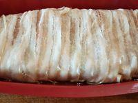 2 - Mettre le four à préchauffer th 6 (180°). Huiler un moule en silicone ou une terrine. Remplir avec la moitié de la farce à la viande, répartir les lamelles de porc en une couche uniforme, compléter avec le reste de la farce à la viande et bien tasser. Terminer en disposant les tranches de lard fumé en les superposant. Placer le moule ou la terrine dans un grand plat rempli d'un fond d'eau, recouvrir le moule de papier aluminium faire un petit trou au milieu pour laisser s'échapper la vapeur(ou la terrine de son couvercle). Placer le tout dans le four th 6 (180°) et faire cuire au bain-marie pendant 1 h. Laisser refroidir dans le four éteint. Placer au réfrigérateur jusqu'au lendemain et déguster coupé en tranches avec une salade et des cornichons.