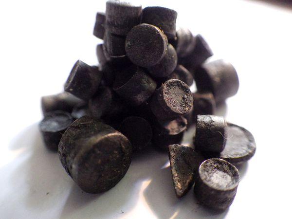 Les gobelets sous les plateaux de pesage sont remplis de divers métaux pour trouver l'équilibre de la balance.