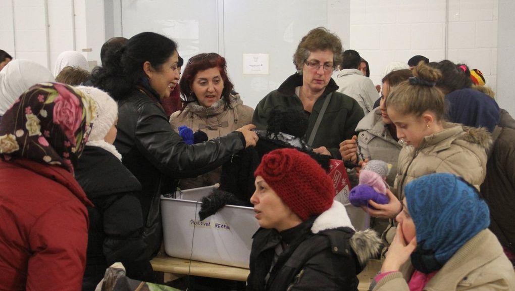 Dicht umringt sind die gemeindliche Kulturreferentin Dr. Martina Edelmann  (re.) und die Veitshöchheimer Dolmetscherin Hayet Jaziri (2.v.l.) von Flüchtlingsfrauen, als Edelmann neue Wolle in die Notunterkunft bringt.