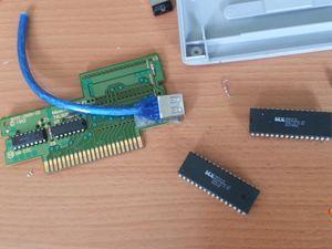Travail d'intégration d'un connecteur USB femelle dans une cartouche de jeu Super Nintendo.