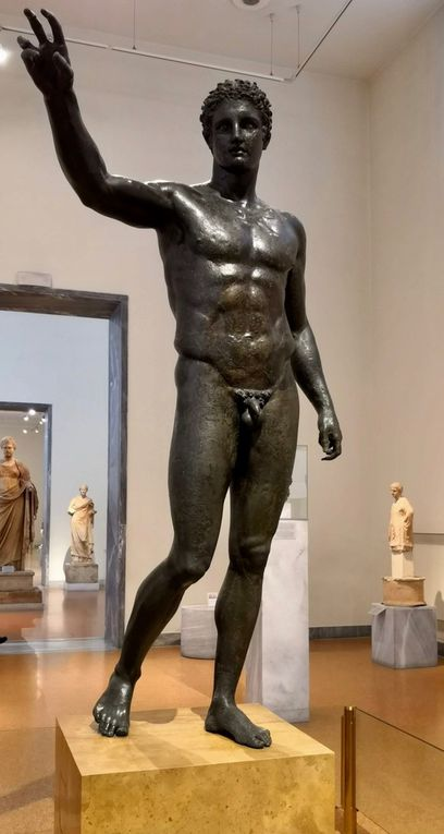 """Bronze statue of a youth. From the Antikythera shipwreck. The figure has been identified with Perseus, holding the head of Medusa. More probably, it depicts Paris, holding the """"apple of Strife"""". Attributed to the Sikyonoan sculptor Euphranor, About 340-330 BC."""