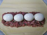 2 - Mettre le four à préchauffer th 6,5 (200°). Une fois les 4 oeufs durs cuits et refroidis, les écaler. Préparer une plaque allant au four et la recouvrir de papier sulfurisé. Y déposer la pâte feuilletée. Placer une couche de farce à la viande (les 2/3 environ)  sur la pâte en prenant soin de laisser la moitié de la pâte libre. Disposer les 4 oeufs durs sur la couche de viande puis recouvrir du reste de farce. Badigeonner le tour de la pâte avec un peu d'eau au pinceau, rabattre le petit côté sur la farce, puis venir recouvrir le tout avec le grand côté de la pâte de façon à bien entourer la farce et réaliser un pâté. Souder les extrémités et dorer le tout avec un jaune d'oeuf. Créer 2 trous sur le dessus du pâté pour y mettre 2 petites cheminées en papier sulfurisé, dessiner des motifs au couteau et mettre au four th 6,5 (200°) pour 45 mn en surveillant. Le pâté doit être bien doré.