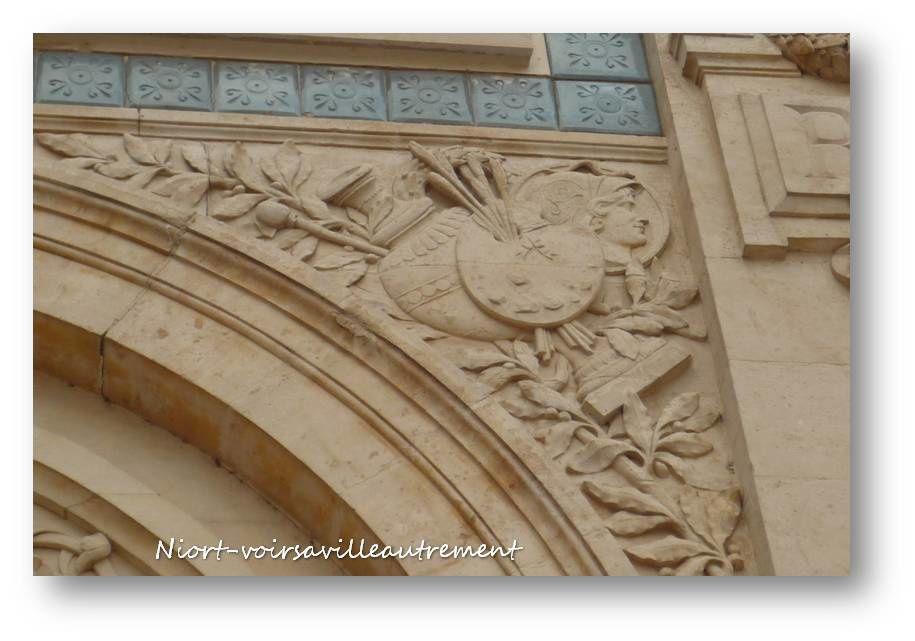 Dans l'écoinçon gauche se trouvent sur un fond de palme les instruments nécessaires à la sculpture et à l'architecture: équerre, compas, règle, plan, chapiteau sculpté, maillet, livre.Dans l'écoinçon droit se distinguent sur un fond de rameau de laurier des objets pour le peintre, un modèle antique (avec casque et serpent sur le casque) dans un médaillon, un vase, une couronne de laurier et surtout une palette avec des pinceaux.