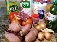 1 - Peler les pommes de terre, réserver en recouvrant d'un sopalin  humide pour ne pas qu'elles noircissent. Couper les tomates en quartiers et les épépiner. Peler les oignons, ainsi que l'ail, ôter le germe central et émincer le tout.  Mettre un fond d'huile à chauffer dans une casserole. Couper un peu de piment rouge en petits morceaux (quantité suivant les goûts) et préparer une belle tranche assez épaisse de jambon Serrano.