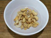 4 - Mettre les noix de cajou à tremper dans un bol avec de l'eau froide. Presser le jus d'un citron jaune. Le verser dans le mixeur, rajouter les raisins secs blonds et mixer le tout, incorporer ensuite les noix de cajou ramollies et égouttées et mixer à nouveau. Diluer l'agar-agar dans une casserole avec l'eau, porter à frémissement, maintenir 10 secondes afin d'obtenir un gel,  et incorporer aussitôt à la préparation et mixer à grande vitesse pendant au moins 30 secondes afin d'obtenir un mélange homogène.