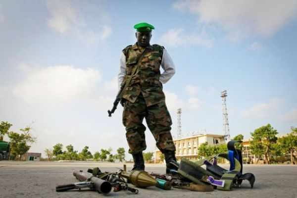 A soldier stands over the weapons seized from four suspected members of Al Shabaab, the Islamic insurgent group, in Mogadishu, Somalia.