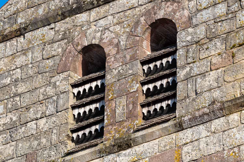 Je remarque que les abat-sons ne sont pas comme souvent de simples planches de bois, ils sont travaillés et recouverts de lauzes. Un grillage empêche les oiseaux de pénétrer dans le clocher.