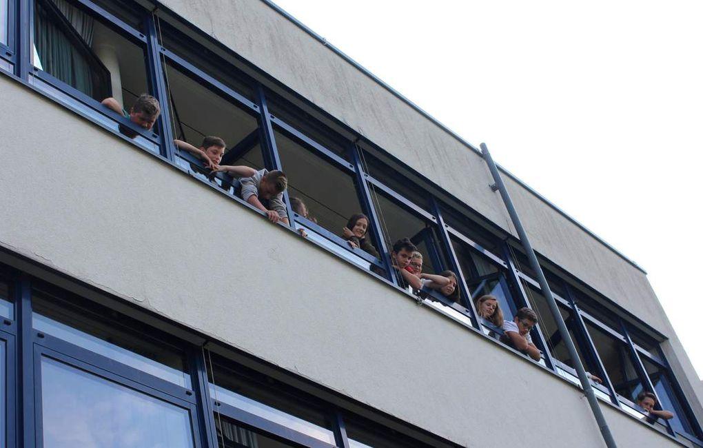 Großes Kino gab es dieser Woche im Freigelände der Mittelschule vor dem Werkraum in Bau IV: Auch Schüler durften die von Falkner Harald Dellert (rechts im grünen Shirt) mit gebrachten Wildvögel auf die ausgestreckte Hand nehmen, so wie im Bild ein Q11ler einen drei Monate alten Bartkauz. Da schauten nicht nur die am Projekt direkt beteiligten Klassen, die Q11 des Gymnasiums und die sechste Klasse der Mittelschule staunend zu. Auch aus in darüber liegenden Fenstern der Mittelschule ließen sich viele Lehrer und Schüler als Zaungäste das seltene Schauspiel nicht entgehen.