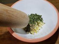 1 - Peler et dégermer l'ail, hacher en petits morceaux. Mettre dans un mortier (ou un bol profond), ajouter le gingembre écrasé au presse-ail, l'origan (facultatif), le persil et piler au mortier.