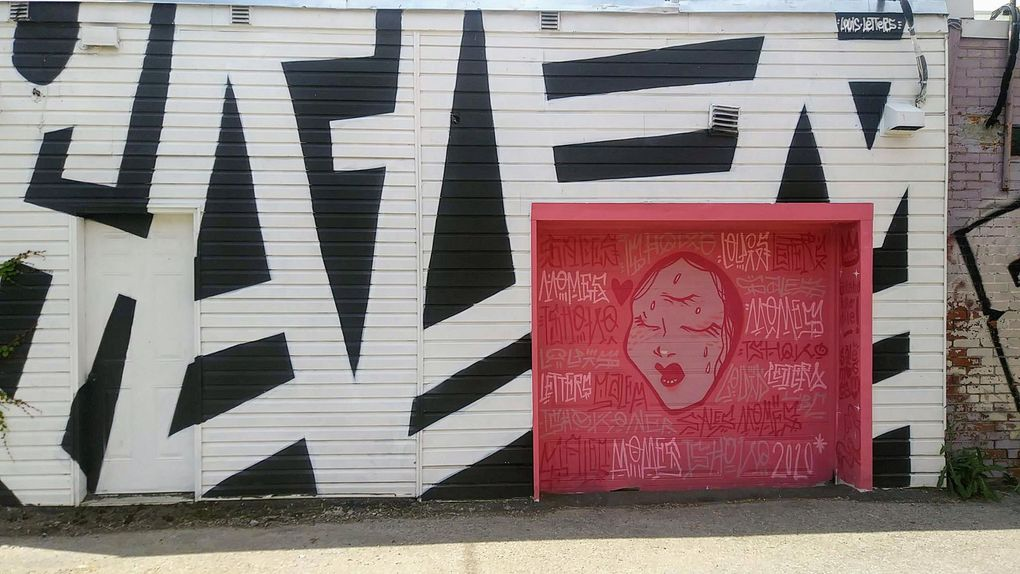 Serein ou triste, ce visage féminin semble transpercer cette porte de garage. Tout autour, des calligraphies de Louis Letters tranchent avec le rose.