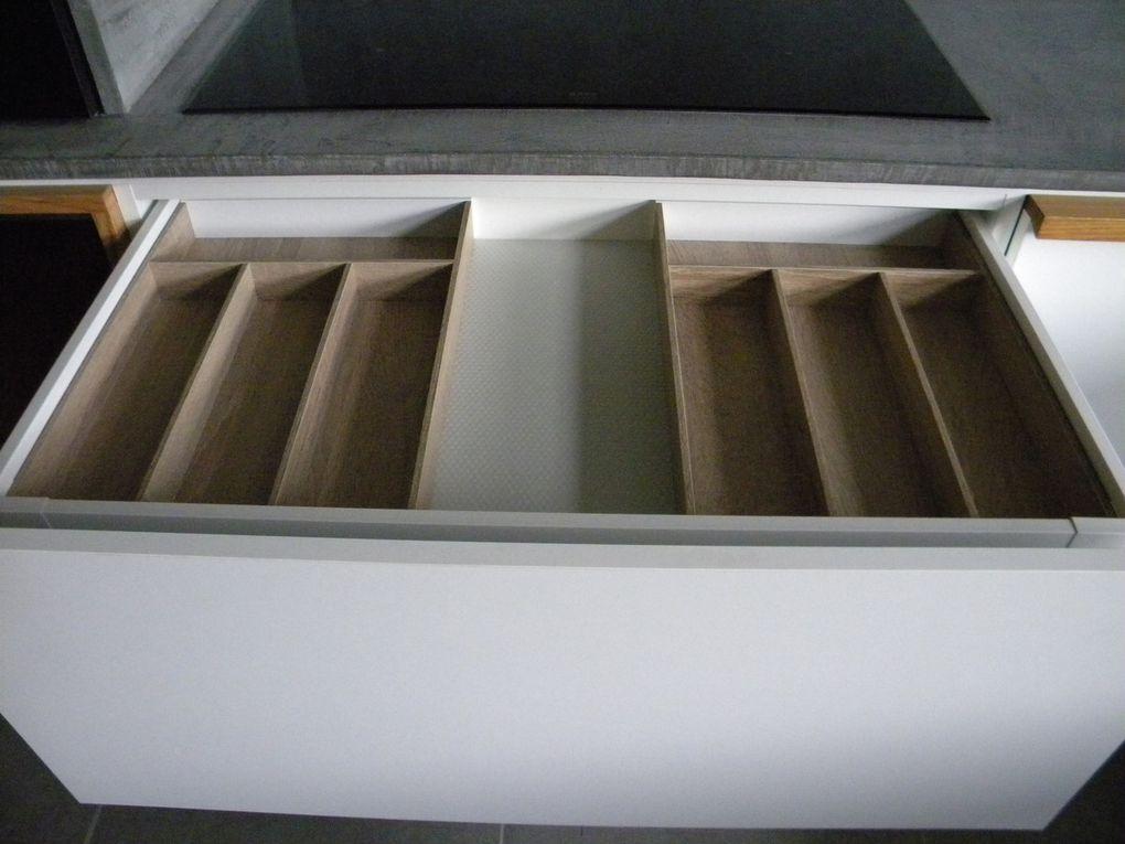 Fabrication propre et sur mesure d'une cuisine réalisée en MDF plaquée chêne vernis pour les éléments en bois et en stratifié (ral gris souris,blanc et noir) pour les éléments de couleur. L'élément séparé est encastré dans le mur et il à 1 partie mobile réalisée en tableau noir aimantée. Les poignées en bois sont de fabrication propre - finition vernis.