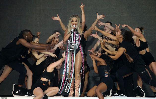 Rita Ora arbore ses jambes aiguisées avec un justaucorps noir et des bretelles à sequins ornés de bejeweled alors qu'elle dirige les stars du bal majestueux Capital FM Summertime Ball
