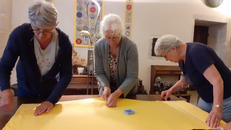 Dominique, Jacqueline et Mireille fixent la foublure avec des épingles.