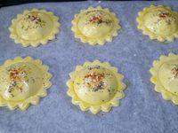 4 - Prélever à l'aide d'un emporte-pièces de 8 cm de diamètre 12 pièces de pâte en forme de fleur. Placer 6 fleurs sur une plaque allant au four recouverte de papier sulfurisé. Déposer au centre de ces 6 pièces un petit tas de farce en laissant 1 cm environ de bord. Avec un pinceau humecter à l'eau le bord de la pâte et venir recouvrir avec une 2ème fleur en pâte, bien souder délicatement les bords, puis à l'aide d'un verre d'un diamètre inférieur à votre fleur, marquer un cercle sur le dôme de chaque pièce (voir photo). Dorer au pinceau avec un jaune d'oeuf dilué dans un peu d'eau (ou de lait) Parsemer de graines de pavot et de sésame, saupoudrer de piment doux ou paprika .... Mettre à cuire au four th 6,5 (200°) pour 10 à 15 mn en surveillant. La pâte doit être bien gonflée et dorée.