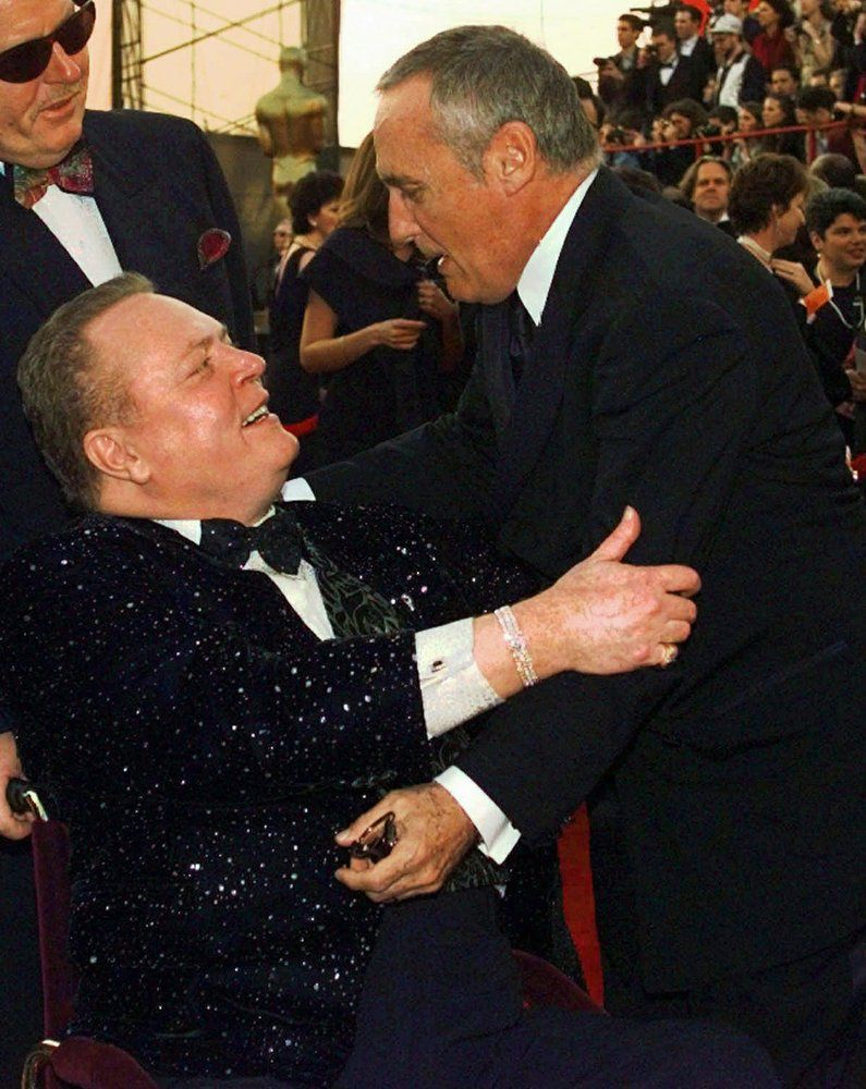 "FILE - Dennis Hopper, right, gives Larry Flynt a hug as they arrive for the 69th Annual Academy Awards on March 24, 1997, in Los Angeles. Flynt, who turned ""Hustler"" magazine into an adult entertainment empire while championing First Amendment rights, has died at age 78. His nephew, Jimmy Flynt Jr., told The Associated Press that Flynt died Wednesday, Feb. 10, 2021, of heart failure at his Hollywood Hills home in Los Angeles. (AP Photo/Michael Caulfield, File)"