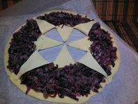 2 - Dérouler la pâte sur du papier sulfurisé. Poser au centre un objet rond (bol, plat, couvercle), appuyer légèrement de façon à marquer la pâte sans la couper ni la trouer. Avec un couteau diviser l'intérieur du cercle en coupant la pâte en 8 parts égales. Répartir ensuite la préparation d'oignons cuits autour du cercle en laissant libre un petit bord extérieur. Rabattre sur les oignons les 8 triangles de pâte découpés du centre vers les bords. Les humecter légèrement avec de l'eau pour bien les coller et les presser légèrement avec une fourchette. faire de la même façon des marques de fourchette sur tout le tour de la pâte.