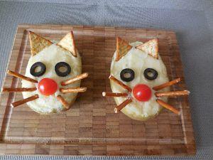2 - Remplir délicatement les coques de pommes de terre de purée. Lisser la surface y déposer successivement ; 2 crackers triangulaires légèrement enfoncés pour matérialiser les oreilles, des rondelles d'olives noires dénoyautées coupées finement pour les yeux, 1/2 tomate cerise en guise de nez et terminer par 3 bretzels coupés en 2 disposés de chaque côté du nez pour créer les moustaches