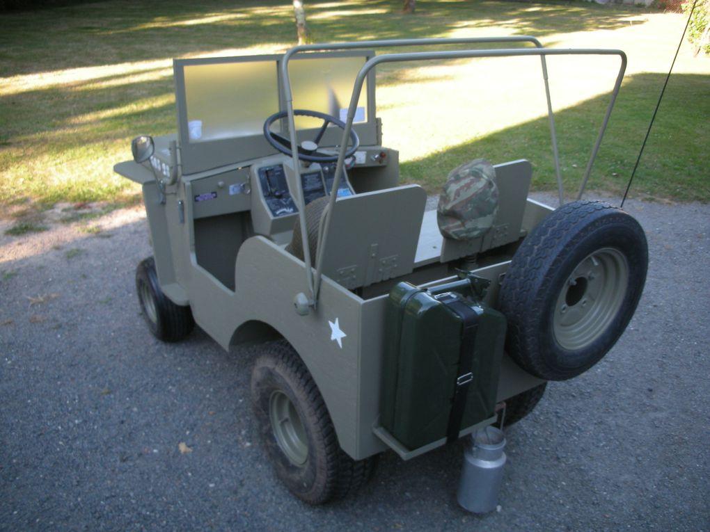 """Jeep """"  Willys  """"   échelle 1/2. Toute la réalisation est faite avec de la récupération, sauf la peinture ! La caisse est en bois contreplaqué, bois compressé. Le capot est en tôle ainsi que le petit capot entre le grand et le pare-brise. Le pare-brise est recouvert de tôle dans sa partie inférieure. (La tôle provient d'anciens panneaux publicitaires 8/10ième) Le pare-brise se repli bien sûr, les feux fonctionnent, les black-out aussi. Vitesse de pointe 8 km/h Pour le nombre d'heures de travail entre 400 et 450 heures  Jean-Pierre Parade, concepteur, propriétaire et conducteur."""