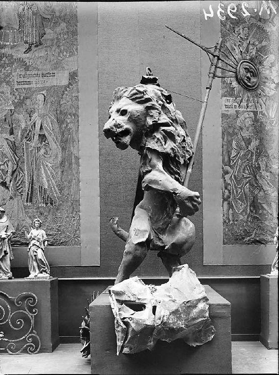 """Paris, Petit Palais, """"Exposition d'oeuvres d'art mutilées ou provenant des régions dévastées par l'Ennemi"""". """"Percé par des obus, le lion de l'Hôtel de Ville d'Arras est conservé à l'abri"""". Il entre dans les collections du Musée des Beaux-Arts vers 1930 et est exposé aujourd'hui dans une galerie du cloître. novembre 1916. (source : ECPAD)"""