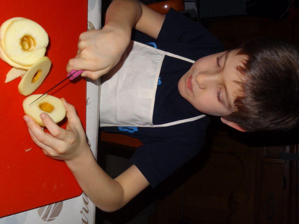 """ÉTAPE N°3: Couper chaque pomme en rondelles et la reconstituer .Super!!! Guillaume s'est débrouillé comme un chef ( son tablier ne ment pas !!!) .On remarque sur l'avant dernière photo la main un """" chouille """" stressée du papa voyant que guillaume arrivé vers la fin de sa pomme ;)"""
