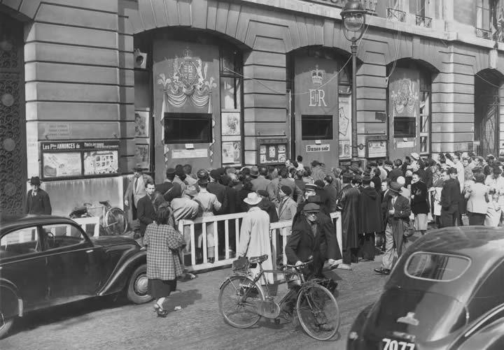 """Des Parisiens se pressent autour des fenêtres du siège du """"Figaro"""" pour regarder le couronnement d'Elizabeth II à la télévision, le 2 juin 1953 à Paris. (KEYSTONE / HULTON ROYALS COLLECTION / GETTY IMAGES)"""
