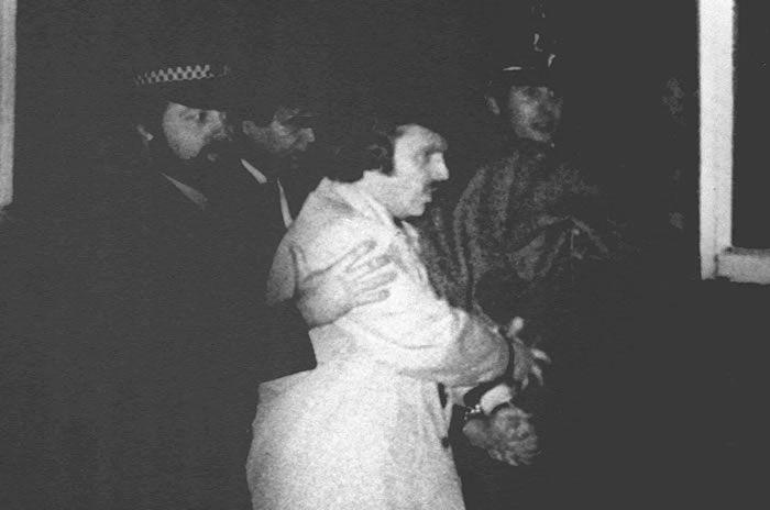 """Peter William Sutcliffe, suspecté d'être """"l'éventreur du Yorshire, est escorté le 06 janvier 1981 à Bradford par des policiers britanniques qui le conduisent à la cour de Dewsbury pour y être entendu et inculpé du 13ème crime commis par l'homme qui a """"fait trembler les villes situées près... Photo AFP"""