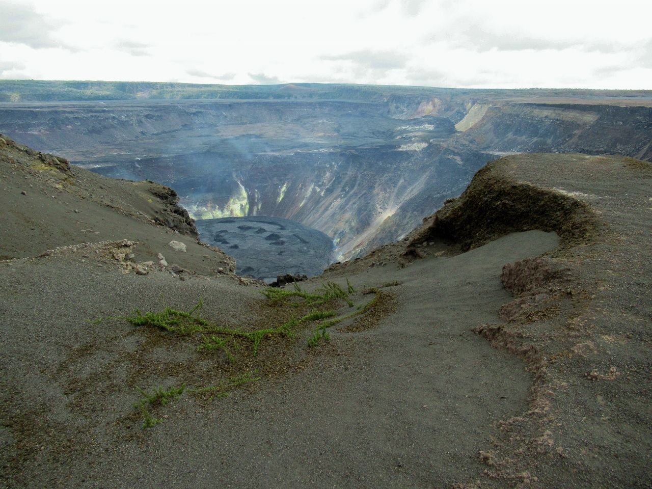 Bluish gas is visible over the lava lake of Halema'uma'u Crater in this image taken from the southwest rim on June 25, 2021 at 12:37 p.m. HST. Although the eruptive activity has paused at the summit of Kīlauea, gases rich in sulfur dioxide can still be seen emanating from the lava lake, mainly along the northern margin, but also at the western vent and along the southern margin. - USGS photo taken by J.M. Chang.