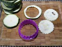 1 - Préchauffer le four th 6/7 (200°). Laver, essuyer et découper la courgette en rondelles sans éplucher. A l'aide d'un emporte-pièce cannelé rond, détailler les tranches de courgettes. Disposer du papier sulfurisé sur une plaque allant au four, huiller légèrement au pinceau avec de l'huile d'olive en répartissant bien sur la feuille de cuisson. Disposer les rondelles de courgettes, les badigeonner d'un peu d'huile, poivrer au moulin et parsemer un peu de fleur de sel sur chaque tranche. Enfourner pour 10 mn environ en surveillant.